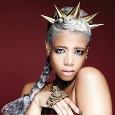 Kelis with extensions a crown or horns adorning her head, smoky eyes and soft lips - one of the looks in her film clip for Acapella